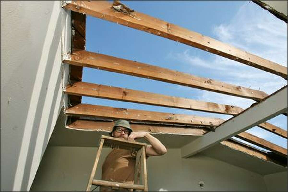Jack Daws plucks a wallboard nail off the top of his ladder as he works on his art installation titled