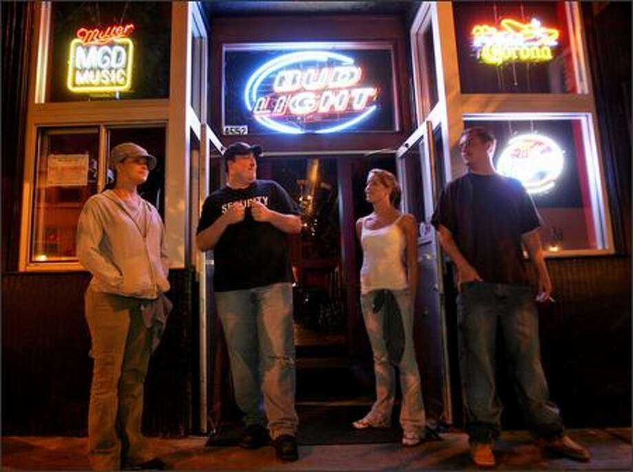 From left, bartender Megan Bloch, who was charged with overserving and with serving a minor; door security man Jason Glockling, who was not charged; barback Tamara Mitchell, who was arrested and charged with overserving; and fill-in cook Mark Milewski, who was not charged, hang out in front of Tommy's waiting for customers. Photo: Mike Urban/Seattle Post-Intelligencer