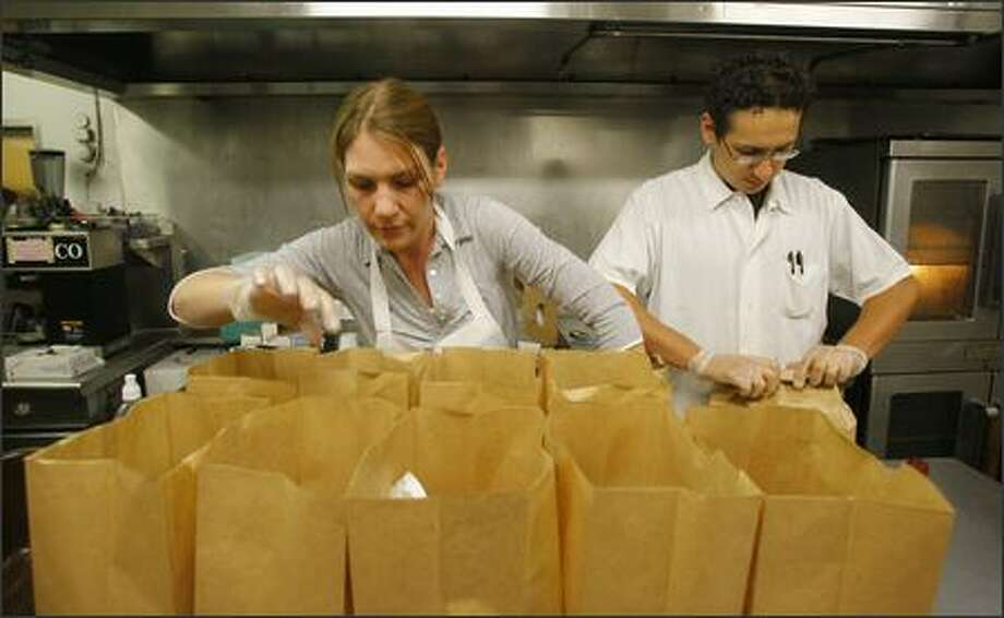 Mezza Cafe kitchen staff Christina Twardokus and CJ Mendoza pack meals destined for a halfway house in Seattle. The cafe, on the third floor of the Starbucks Center, is run by Pioneer Human Services, one of the nation's largest non-profit social service agencies. Photo: Gilbert W. Arias/Seattle Post-Intelligencer