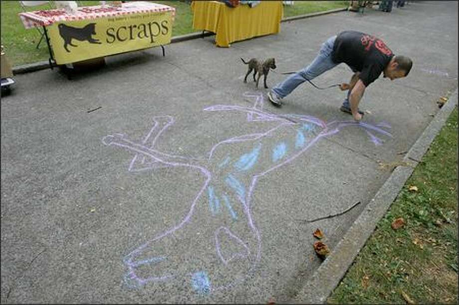 Clifford Tatum uses sidewalk chalk to make a drawing of his dog Jasper while attending a neighborhood party at Denny Park to raise awareness of the park and ongoing improvement efforts. Photo: Gilbert W. Arias/Seattle Post-Intelligencer
