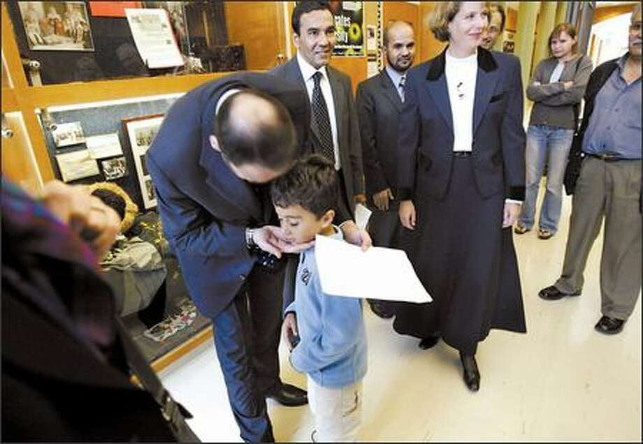 Ustad Atta Mohammad Noor, governor of Afghanistan's Balkh province, thanks Coe Elementary first-grader Zachary Harvey for a welcome card written in Farsi. Noor spoke at the school Monday as part of a cultural exchange project started by Julia Bolz, right. Photo: Andy Rogers/Seattle Post-Intelligencer