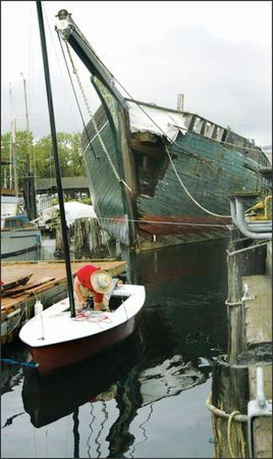With the historic schooner Wawona moored behind him, Sterling Hines-Elzinga, 14, an intern at the Center for Wooden Boats, cleans his personal sailboat in South Lake Union recently. Photo: Andy Rogers/Seattle Post-Intelligencer