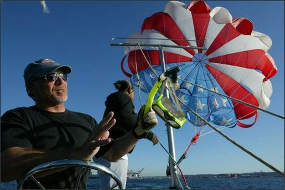 """Steve Arbaugh of Pier 66 Parasail goes out for a run on Elliott Bay in August. """"People think they can only do this when it's sunny,"""" he says. Photo: Karen Ducey/Seattle Post-Intelligencer"""
