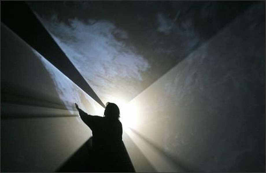 """The audience can walk through the walls in Anthony McCall's """"Doubling Back."""" The walls are projections made of light visible through a mister. Standing is Ruth True, who co-founded Western Bridge with her husband, Bill. Photo: Gilbert W. Arias/Seattle Post-Intelligencer"""