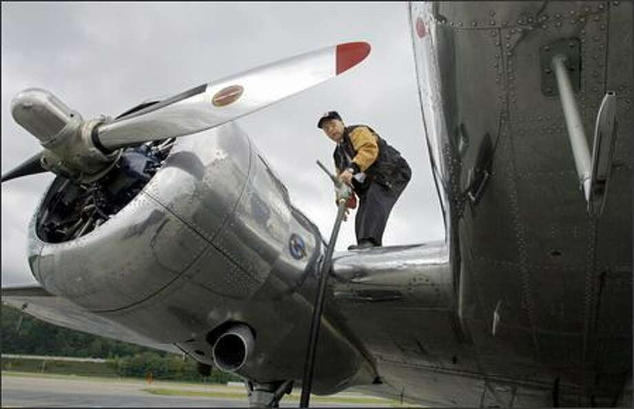 Captain Gerry Norberg, a pilot with Air Canada, refuels a vintage 1937 Lockheed L10A at Boeing Filed on Thursday. Photo: Gilbert W. Arias/Seattle Post-Intelligencer