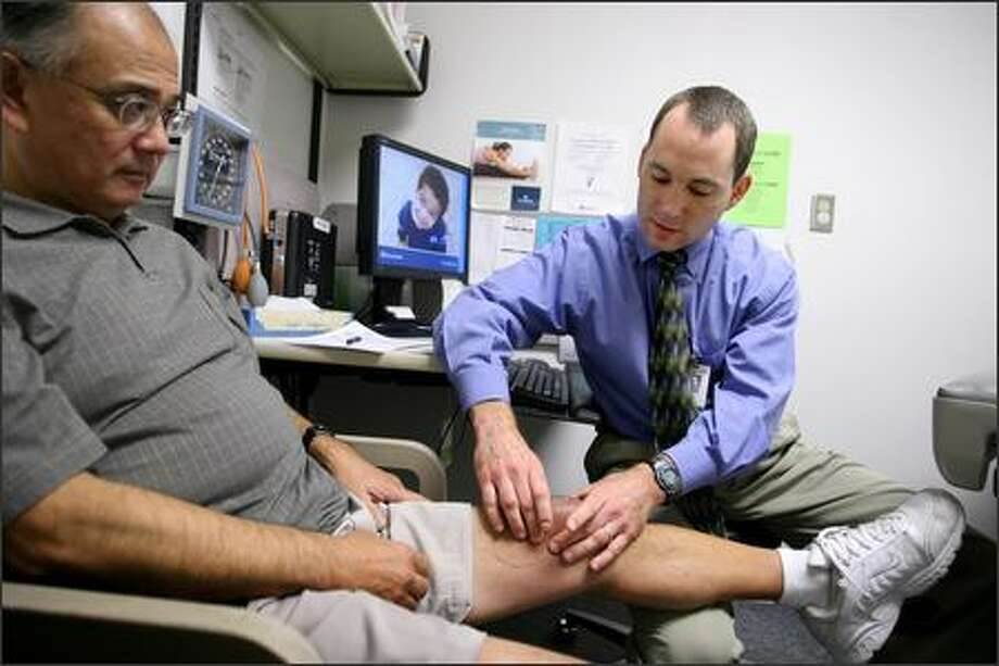 """Dr. Eric Seaver examines Russell Akiyama's knee Tuesday. Seaver, a Group Health physician, regularly e-mails his patients. """"I can provide better care to patients ... because I can now communicate with them on a weekly basis and make adjustments faster than I could if I was seeing these patients every three months in my office."""" Photo: Scott Eklund/Seattle Post-Intelligencer"""
