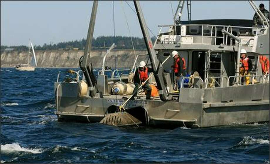 A crew from Evans Hamilton, a nationwide oceanographic consulting firm, on Wednesday removes equipment that measures tidal currents from Puget Sound in Admiralty Inlet off Whidbey Island. Photo: Dan DeLong/Seattle Post-Intelligencer