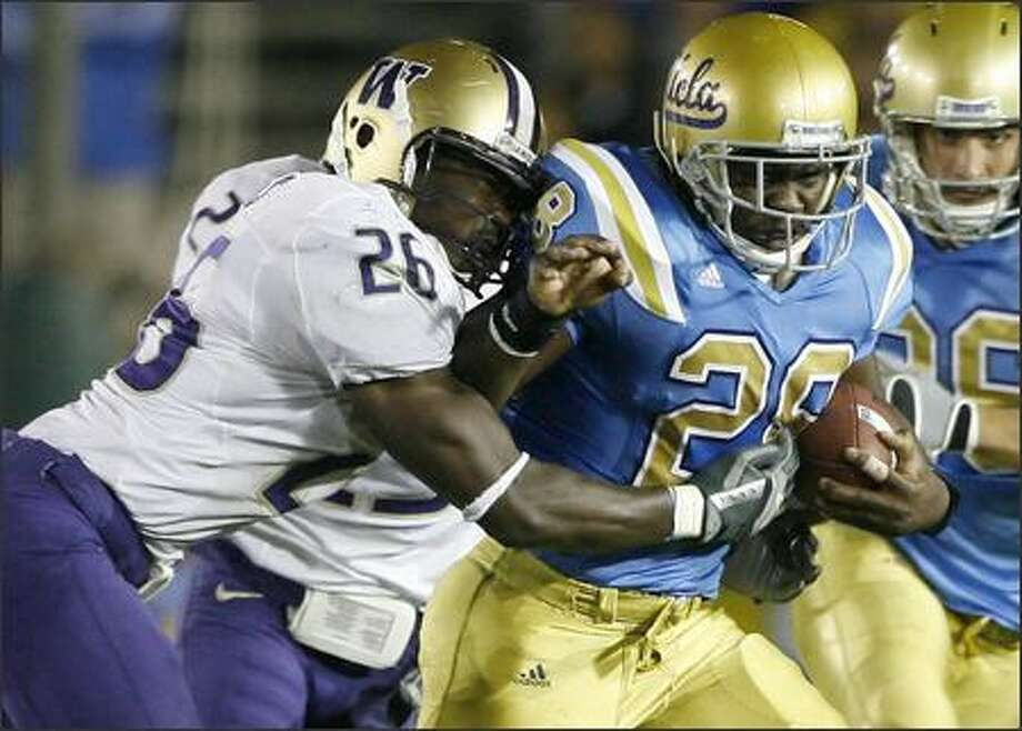 UCLA's Chris Markey (28) is tackled by Washington's Jason Wells (26) after rushing for a first down during the first half. (AP Photo/Gus Ruelas) Photo: / Associated Press