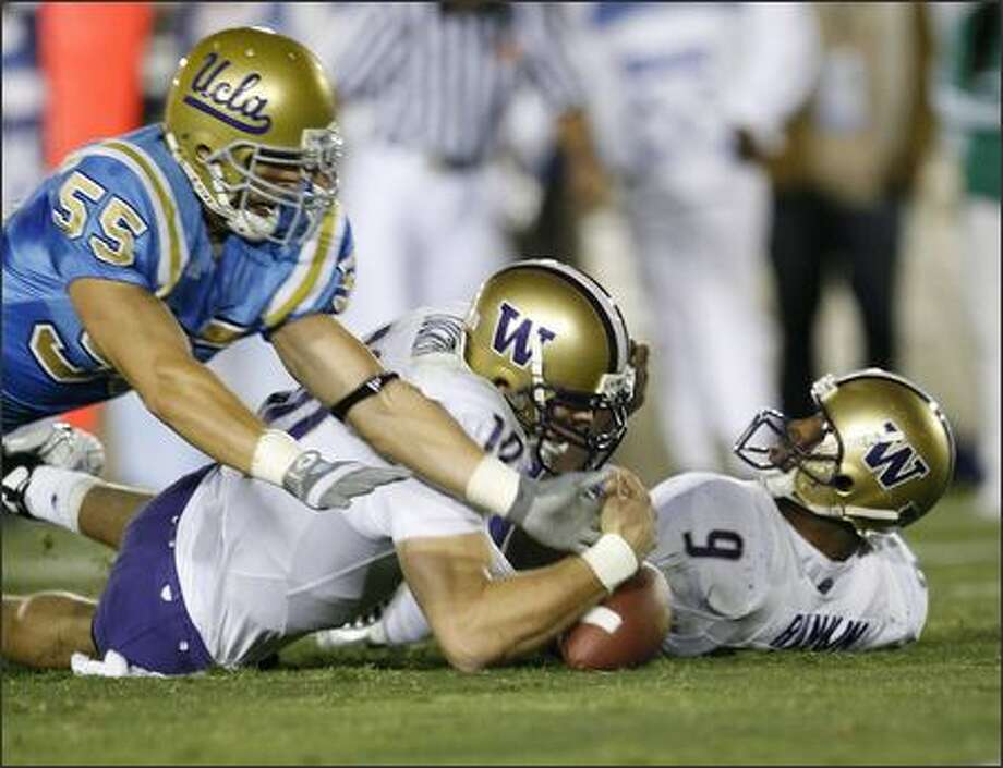Washington quarterback Jake Locker (10) and Louis Rankin (9) attempt to recover their own fumble as UCLA's Korey Bosworth (55) attempts to steal during the first half. (AP Photo/Gus Ruelas) Photo: / Associated Press