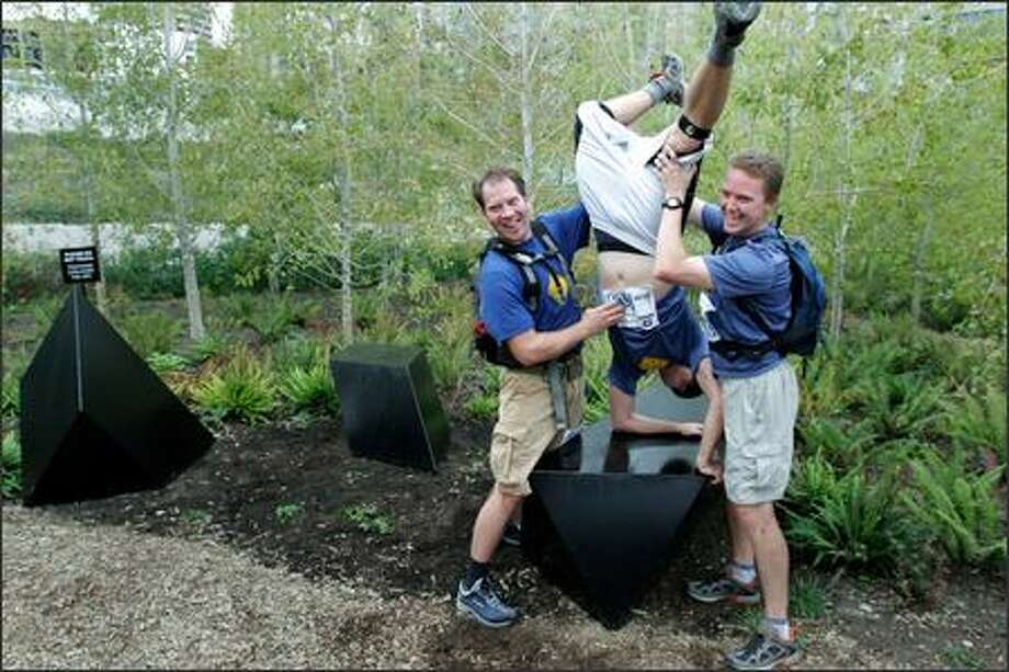 "John Wilkens of Bellingham, left, and Dean Peterson of Seattle hold up their teammate Brian Barr of Lake Forest Park for a photo as evidence they found ""Wandering Rocks"" inside the Olympic Sculpture Park for the ""urban adventure"" race. They were not aware that they weren't supposed to touch the sculpture. Photo: Meryl Schenker/Seattle Post-Intelligencer"