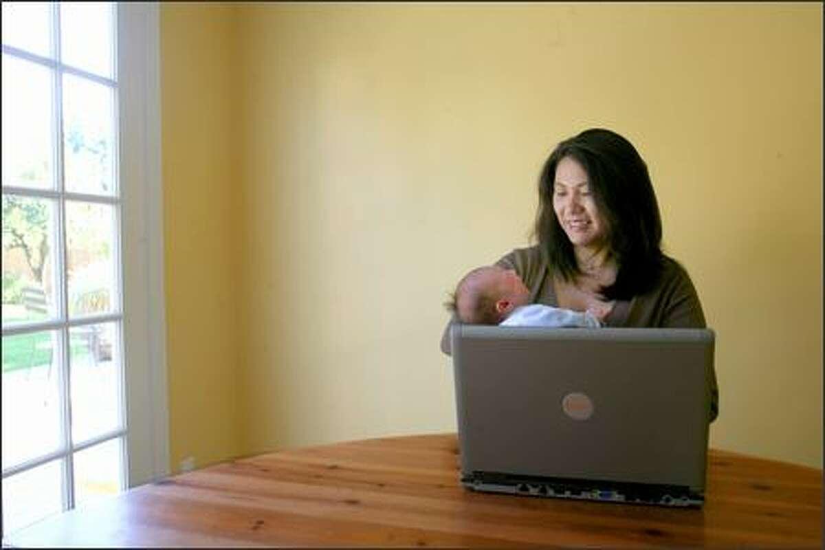 UW professor Yoky Matsuoka, holding her 2-week-old son, won the award for her neuro-robotics work.