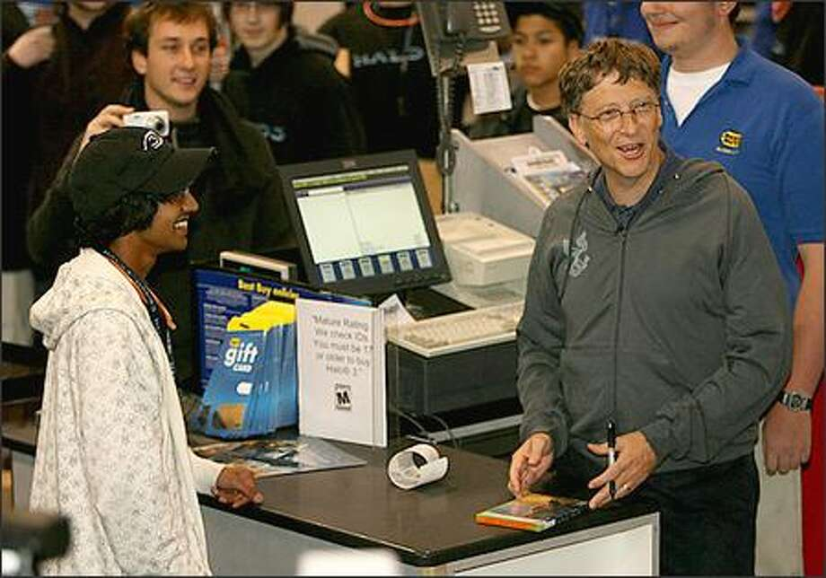 "Microsoft Corp. founder Bill Gates jokes with the assembled media at Best Buy in Bellevue as he signs the first copy of ""Halo 3"" sold to Ritesh David, 17, of Bellevue, on Tuesday. Photo: Mike Urban/Seattle Post-Intelligencer"