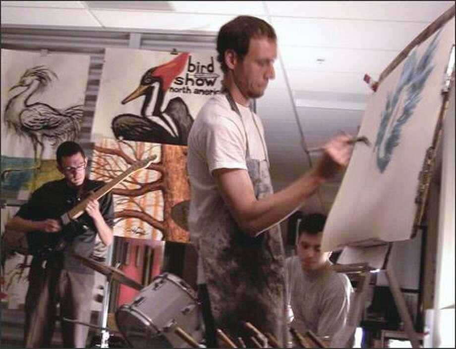 Curtis Poortinga paints a bird while guitarist Ian Peters strums and CJ Miller drums. Photo: /