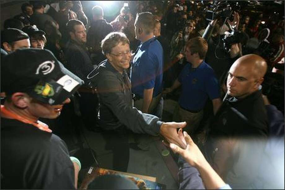 "Bill Gates shakes hands with gamers who had lined up at Best Buy in Bellevue to buy ""Halo 3"" when it went on sale at midnight Tuesday. Photo: Mike Urban/Seattle Post-Intelligencer"