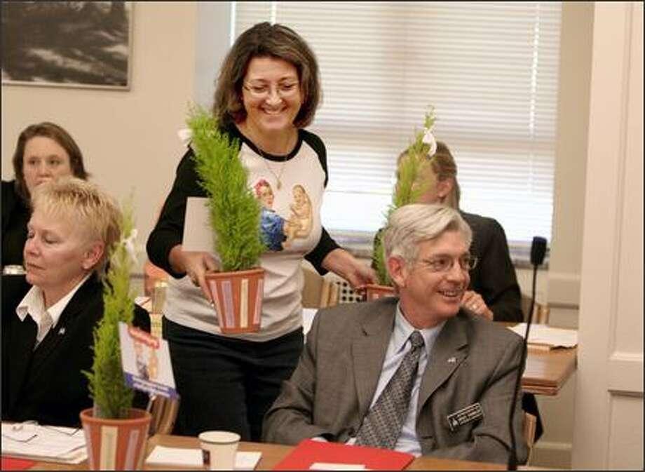 "Diane Arnold of MomsRising.org delivers a tree thanking task-force member Rep. Bruce Chandler, R-Granger, for ""helping Washington's families grows stronger."" Photo: Scott Eklund/Seattle Post-Intelligencer"
