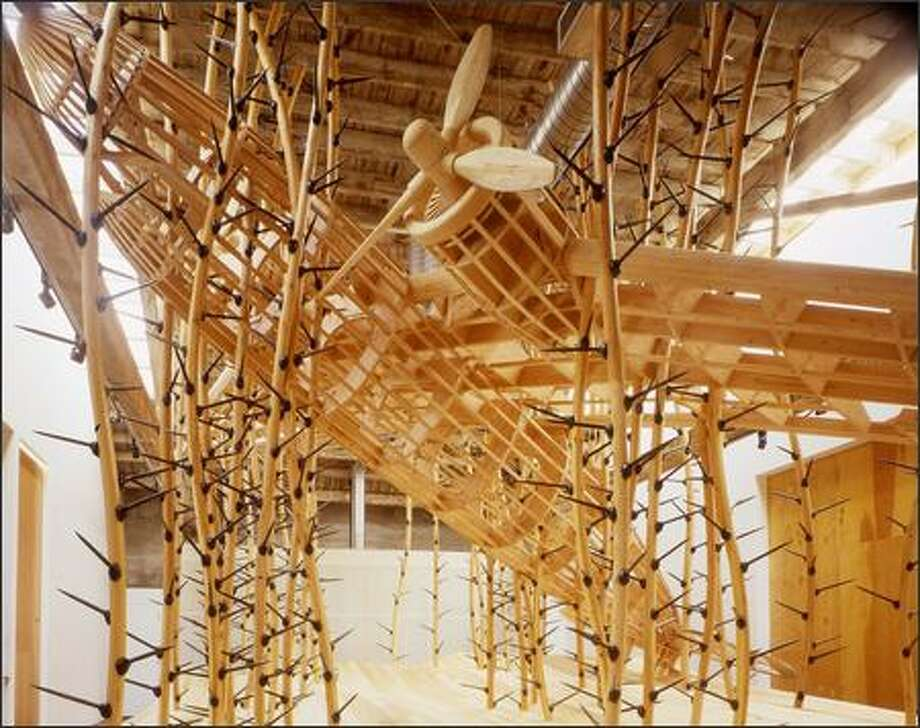 "Wooden thorny vines appear to be reclaiming a crashed skeletal plane in Mike Rathbun's installation, ""N47°36.878' W122°20.788' ,"" at Suyama Space. Photo: Eduardo Calderon"