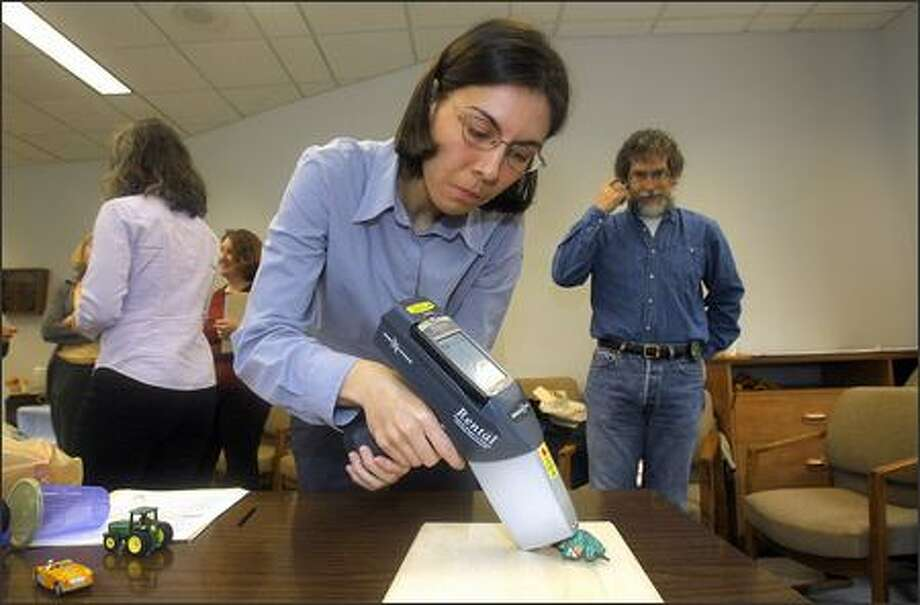 Maria Mergel, a scientist with the Washington Toxics Coalition, checks a toy solider for heavy metals during Thursday's toy-testing day in Olympia for state legislators, their staff and others. Photo: Gilbert W. Arias/Seattle Post-Intelligencer