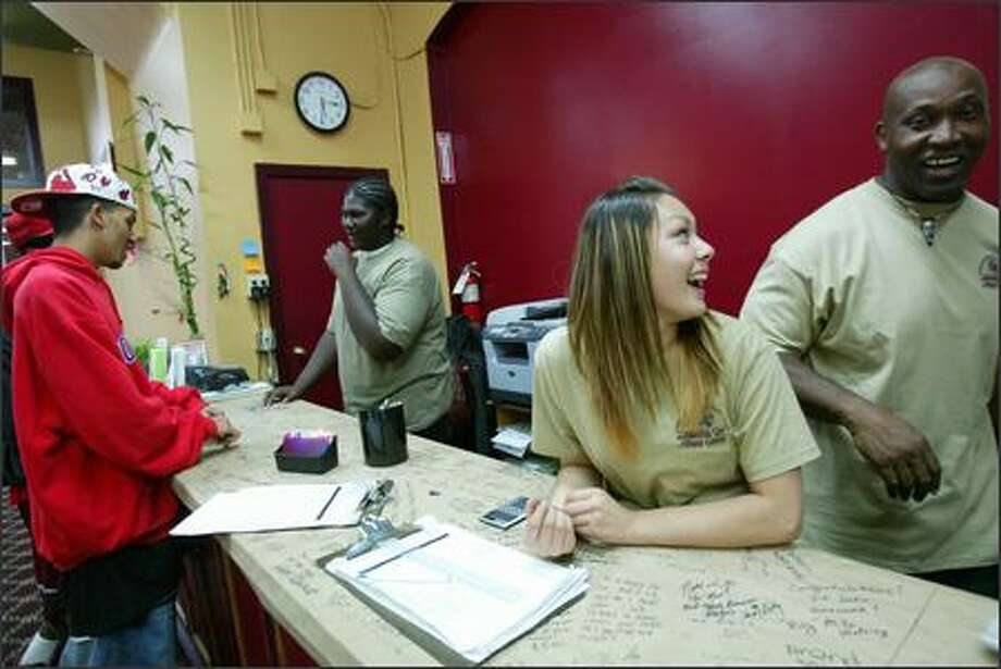 """Michael Townsend, 18, left, visits Nathan Wrice, 17, who works at the Columbia Fitness Center with Julie Le, 15. Owner Bull Stewart, right, hires young people who may have gotten in trouble in the past and helps them turn their life around. """"Every kid deserves a second chance, I don't care what they've been through,"""" he says. Photo: Karen Ducey/Seattle Post-Intelligencer"""