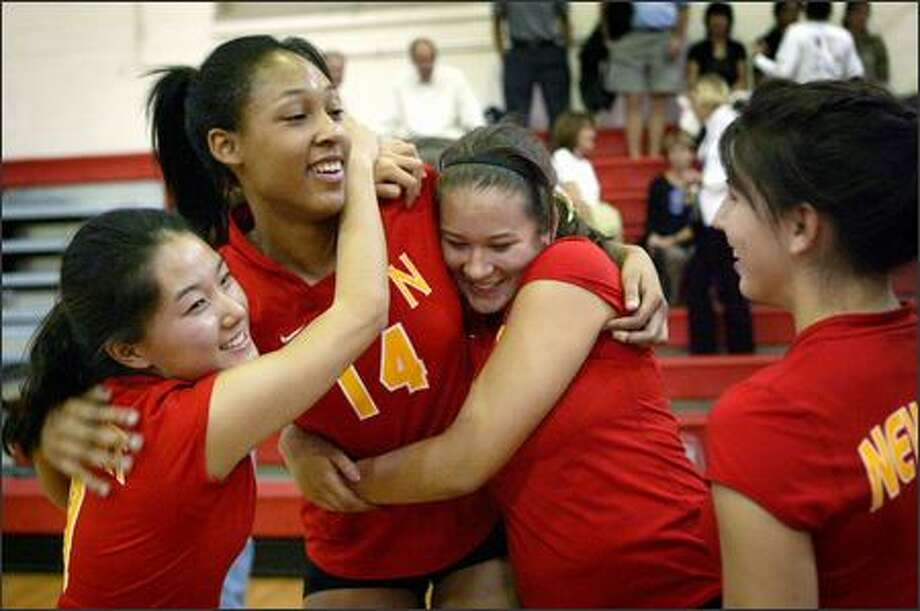 Lauren Barfield gets hugs from Newport teammates Lauren Sakahara, left, and Hannah Tanaka after a win against Sammamish. Photo: Joshua Trujillo/Seattle Post-Intelligencer