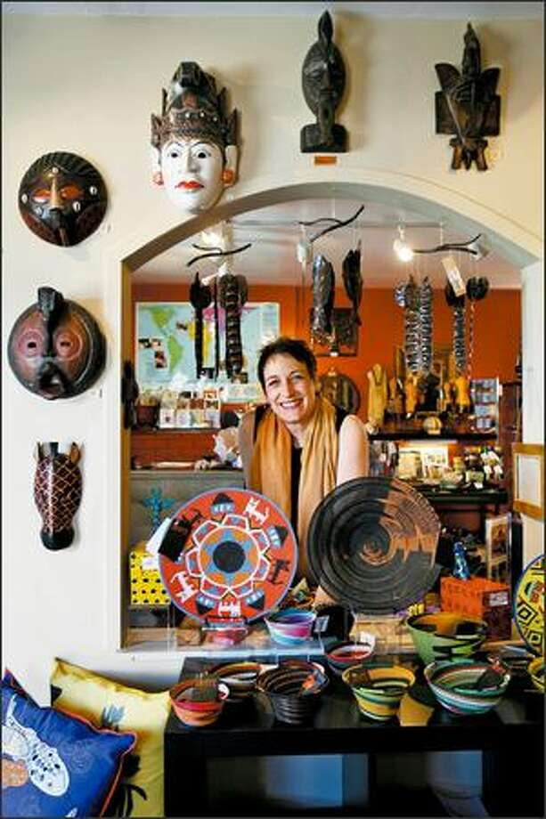 Giraffe Global Gallery's Priscilla Schleigh Kimmel is surrounded by masks from Ghana, steel-drum chimes from Haiti and telephone-wire baskets from South Africa. Photo: Mike Urban/Seattle Post-Intelligencer