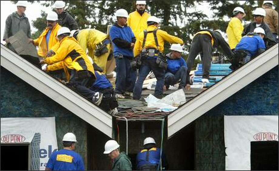 "Volunteers work Sunday on the roof of the new home of Connie Chapin and her four children as part of the television show ""Extreme Makeover: Home Edition."" Photo: Joshua Trujillo/Seattle Post-Intelligencer"