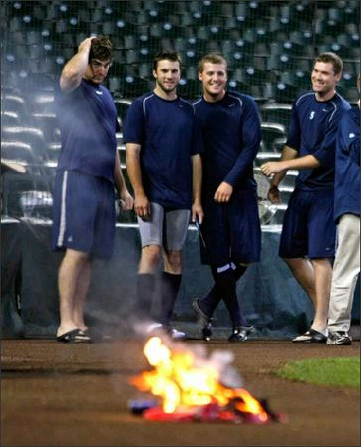 Ryan Rowland-Smith, Brandon Morrow, Eric O'Flaherty and Sean White destroy the backpack. Photo: / Associated Press