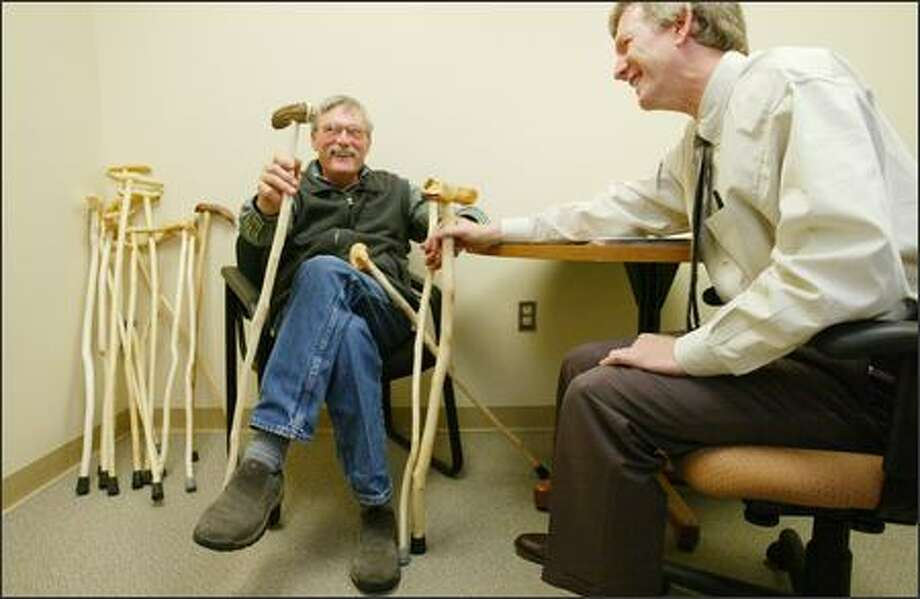 Multiple sclerosis patient Mike Hunter, left, jokes Monday with Dr. James Bowen at Evergreen Hospital in Kirkland. Hunter makes canes for other MS patients. Photo: Paul Joseph Brown/Seattle Post-Intelligencer