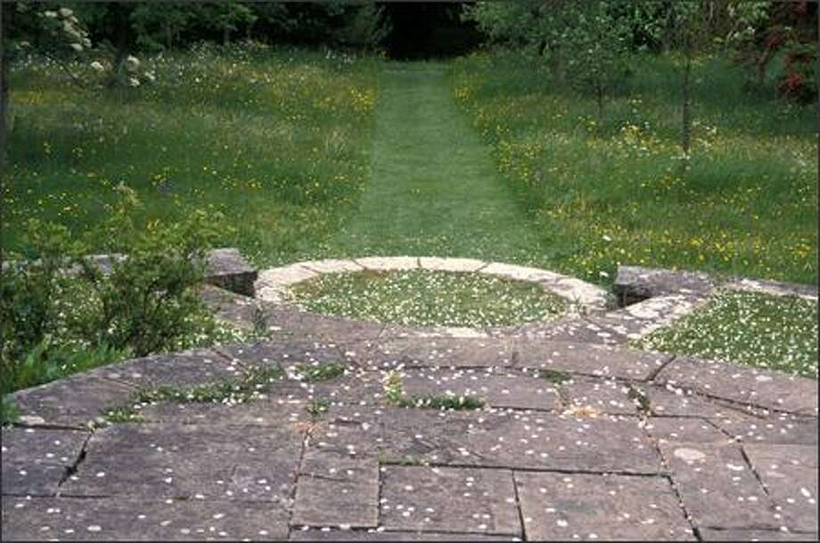 Some gardens in Great Britain are models of shapliness. At Lady Farm in Somerset, a circle of lavender leads to a rectangular gravel path with geometric waves of boxwood and sheared yew. At Bosvigo in Cornwall, left, round and square shapes contrast and complement. Photo: Marty Wingate/for The Seattle Post-Intelligencer