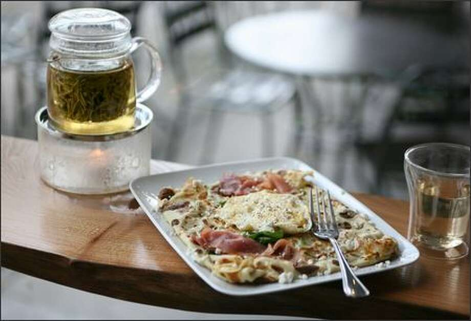 """The savory """"Christy"""" crepe at Miro Tea is filled with Serrano ham, goat cheese and spinach, then topped with a poached egg. Mountain of Jade green tea is among the 250 teas available at the Ballard cafe. Photo: Paul Joseph Brown/Seattle Post-Intelligencer"""