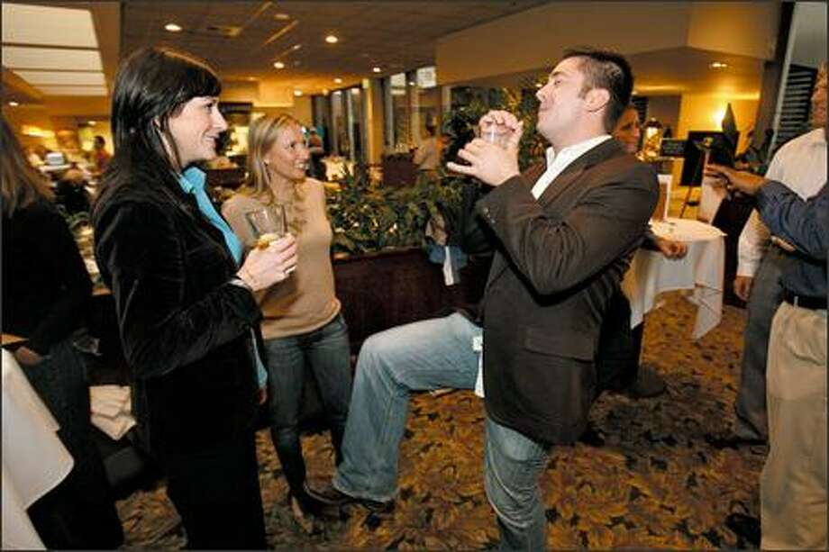 Jabez LeBret explains how he acted the part of a rock star in a recent photo shoot to new friends Katy Willis, left, and Jennifer Wilson during a Just Cauz fundraiser. Photo: Mike Urban/Seattle Post-Intelligencer
