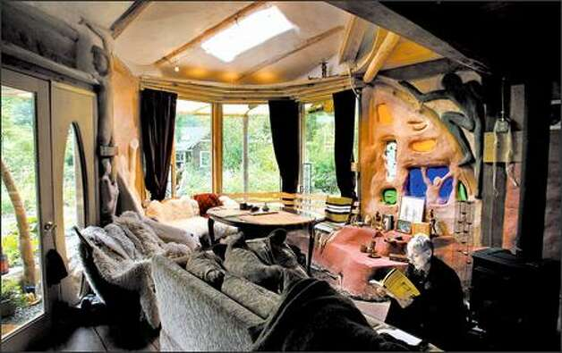 Cate Buck reads in the living room of her cozy, 560-square-foot cob house. Cob is an adobelike mix of clay, sand and straw that traditionally is formed by hand into curvy, sinuous shapes. The building method is making a comeback among green-minded consumers. Photo: Dan DeLong/Seattle Post-Intelligencer