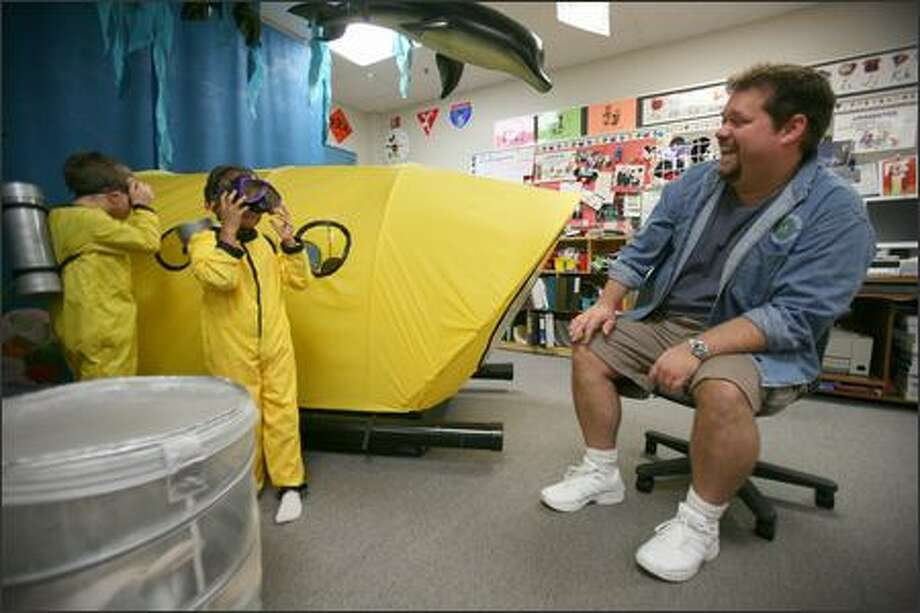 Jeff Thompson, an award-winning kindergarten teacher at Evergreen Elementary School on Fort Lewis, helps 5-year-old students Brayden Murdock, left, and Hannah Hoff with a pretend scuba-diving mission Thursday. The elementary school specializes in helping young students cope with military life. Photo: Paul Joseph Brown/Seattle Post-Intelligencer