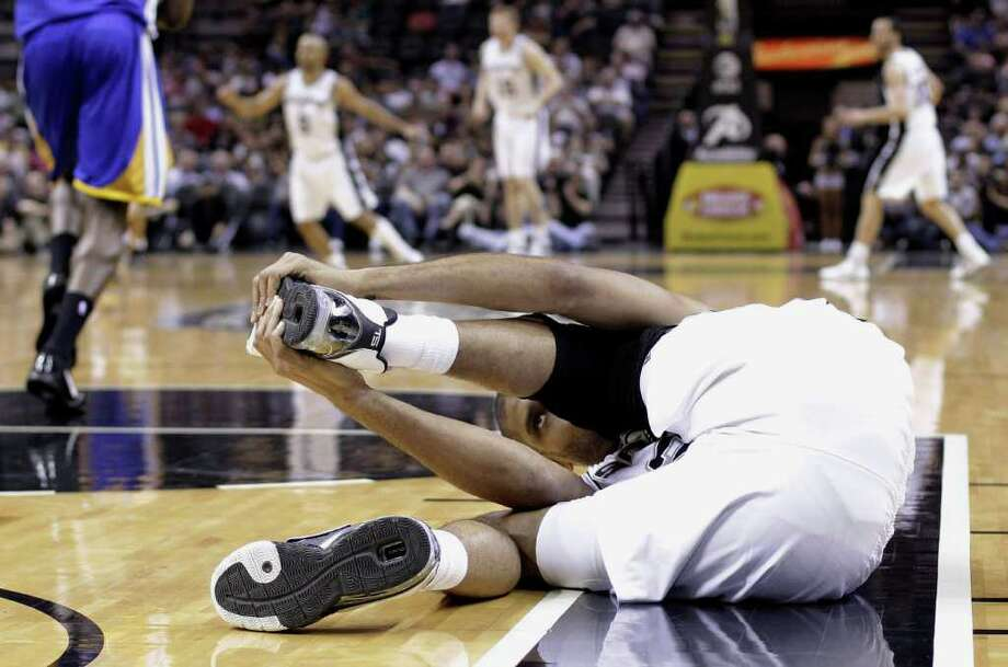 San Antonio Spurs' Tim Duncan holds his left foot after he sprained his left ankle during the first quarter of an NBA basketball game against the Golden State Warriors, Monday, March 21, 2011, in San Antonio. Photo: AP