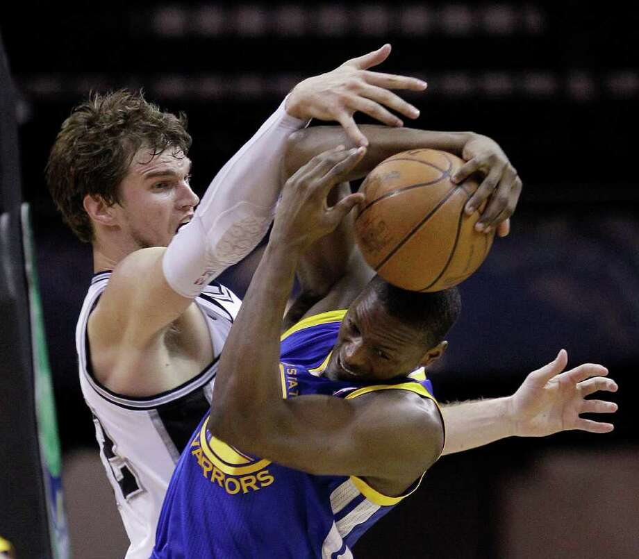 San Antonio Spurs' Tiago Splitter, left, of Brazil, and Golden State Warriors' Al Thornton, right, scramble for a rebound during the third quarter of an NBA basketball game, Monday, March 21, 2011 in San Antonio. San Antonio won 111-96. Photo: AP