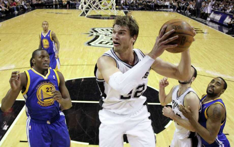 San Antonio Spurs' Tiago Splitter (22), of Brazil, pulls down a rebound as Golden State Warriors' Al Thornton (23) and Reggie Williams, right, look on during the fourth quarter of an NBA basketball game Monday, March 21, 2011, in San Antonio. San Antonio won 11-96. Photo: AP