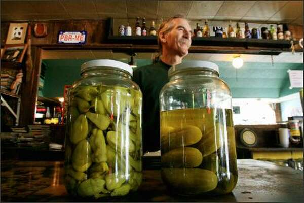 Howard Brown, 59, talks with a customer while tending bar at the Eastlake Zoo Tavern. Bringing back pickles is just one of the many changes Brown has made since being called upon by the bar's owner to help save it from its dire financial situation. Brown first worked at the Zoo from 1978 to 1992.