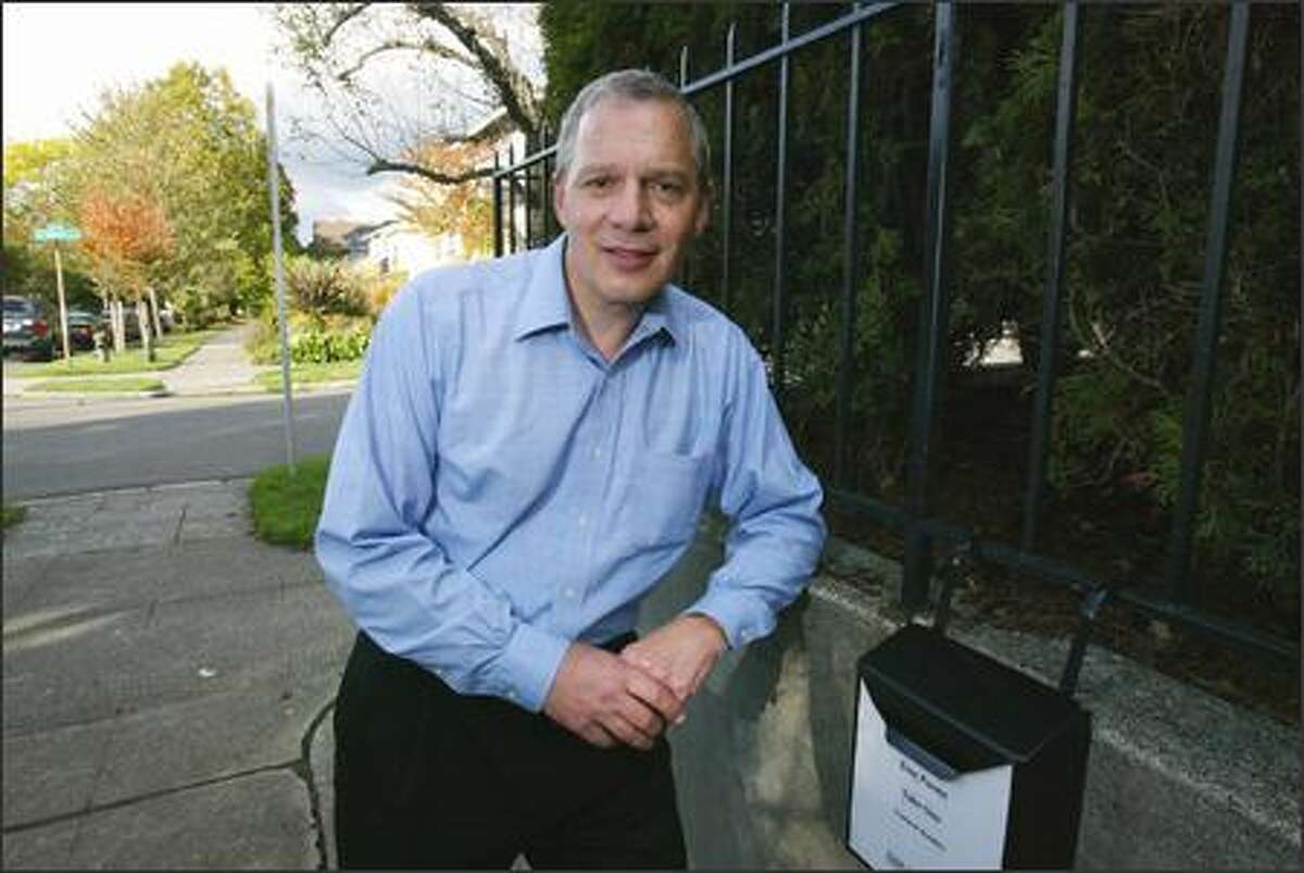 Guy Holliday poses next to a mailbox outside his Capitol Hill home last week. The box contains copies of his original poems for people walking by to pick up and read.