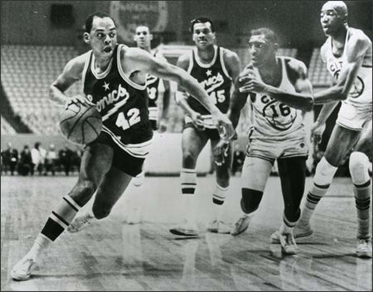 Walt Hazzard, the Sonics' leading scorer during their expansion season, drives to the basket against the Warriors early in the 1967-68 season. Warriors defenders are Al Attles (16) and Nate Thurmond (far right). The game was played at the Cow Palace in San Francisco.