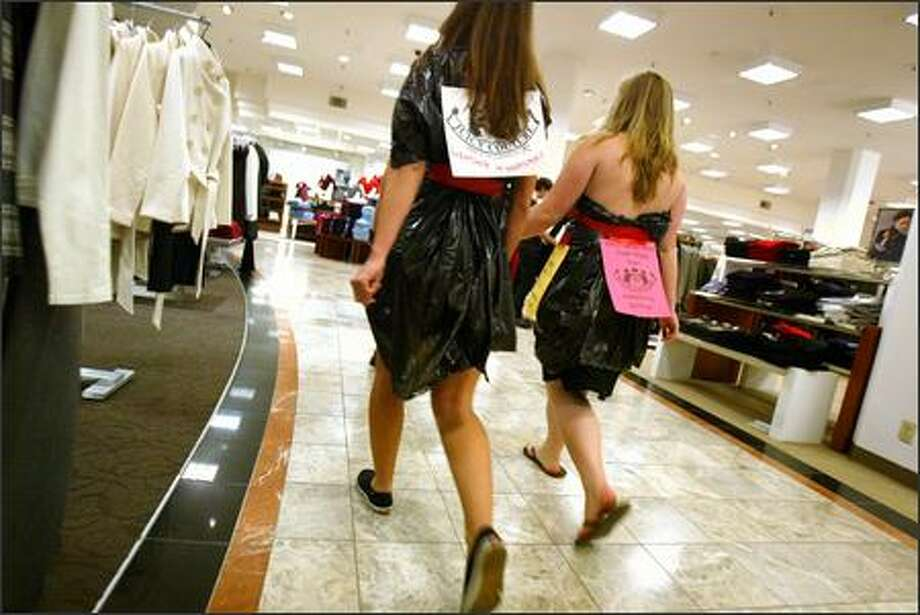 """Bearing signs proclaiming, """"I'd rather wear trash bags than Macy's sweatshop clothing,"""" two students from the University of Washington walk through Macy's department store wearing trash bags to voice their concerns over Macy's hiring non-unionized workers for factory work in Guatemala. Photo: Karen Ducey/Seattle Post-Intelligencer"""