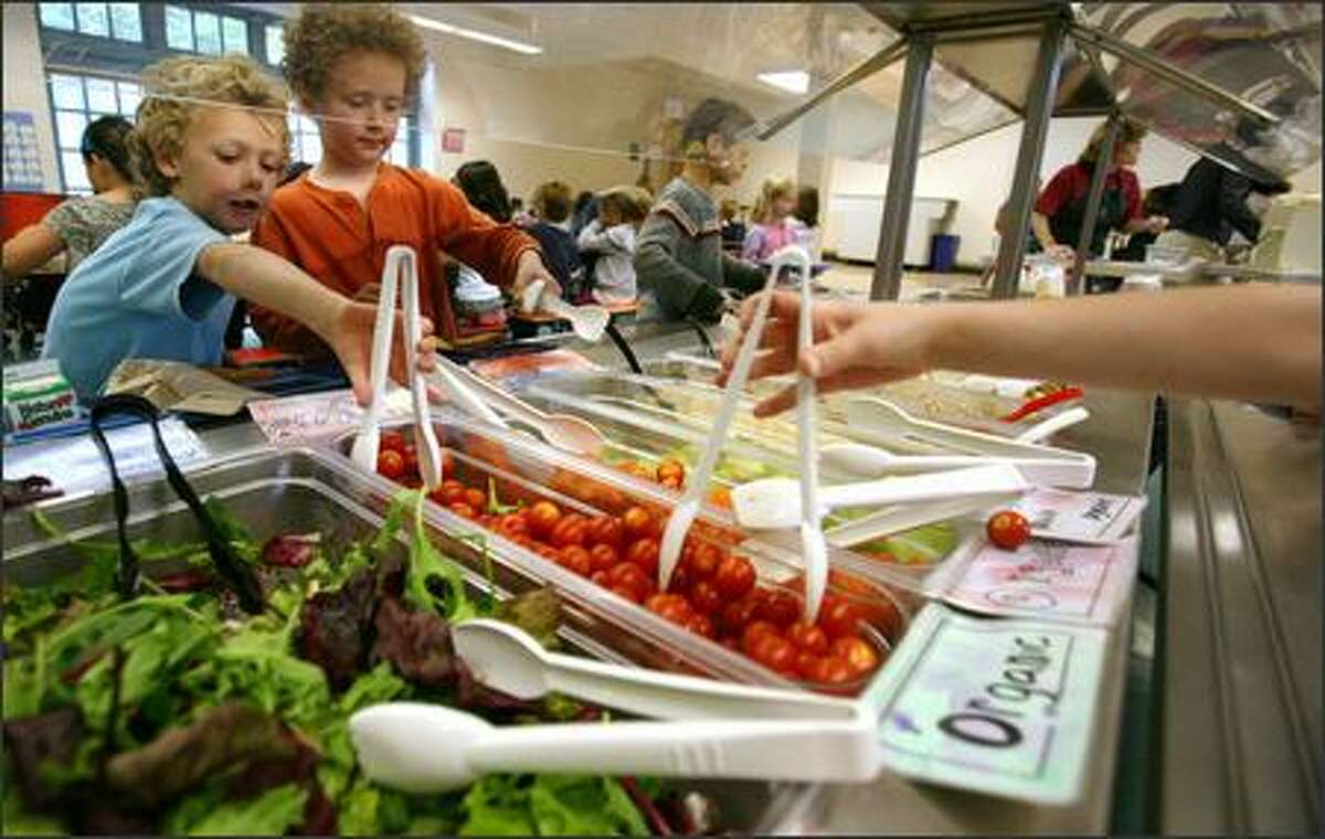 Sam Harburg and Merrill Llewya, students at Lincoln Elementary School in Olympia, dig into the organic salad bar during lunch period.
