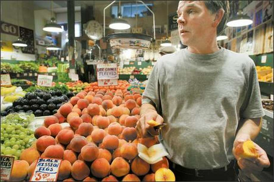 Top produce seller Mike Osborn offers slices of the last local peaches of the season to shoppers at Sosio's Produce on Wednesday in the Pike Place Market. Photo: Dan DeLong/Seattle Post-Intelligencer