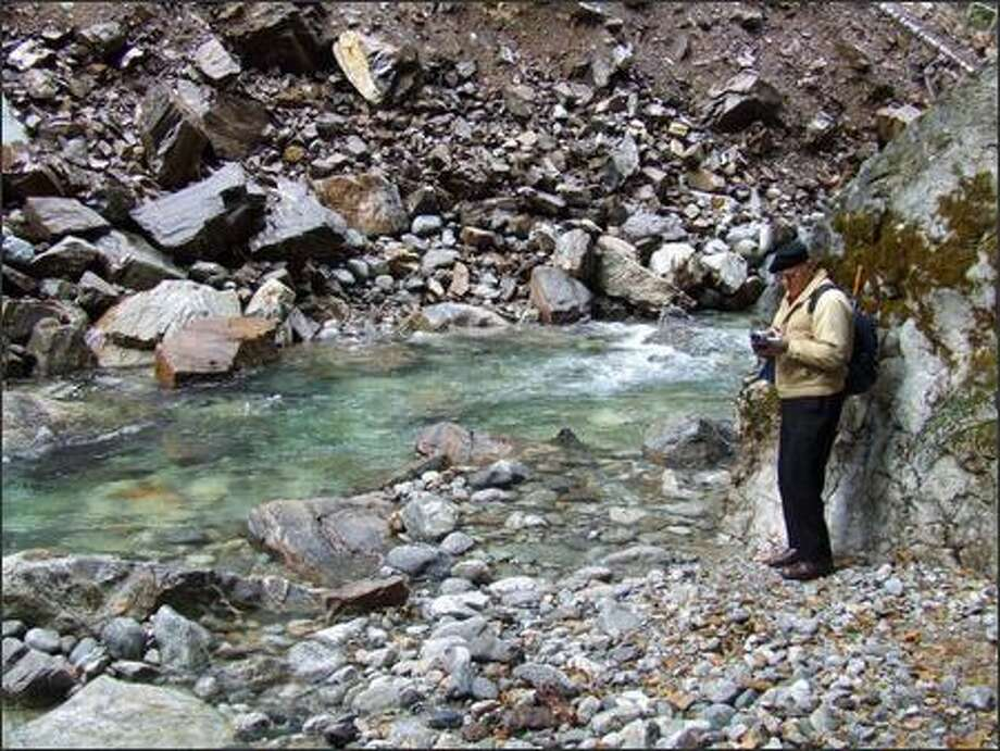 A hiker records the sights and sounds of Stetattle Creek near trail's end; the route is heavily damaged past this point. Photo: Karen Sykes/Special To The Post-Intelligencer