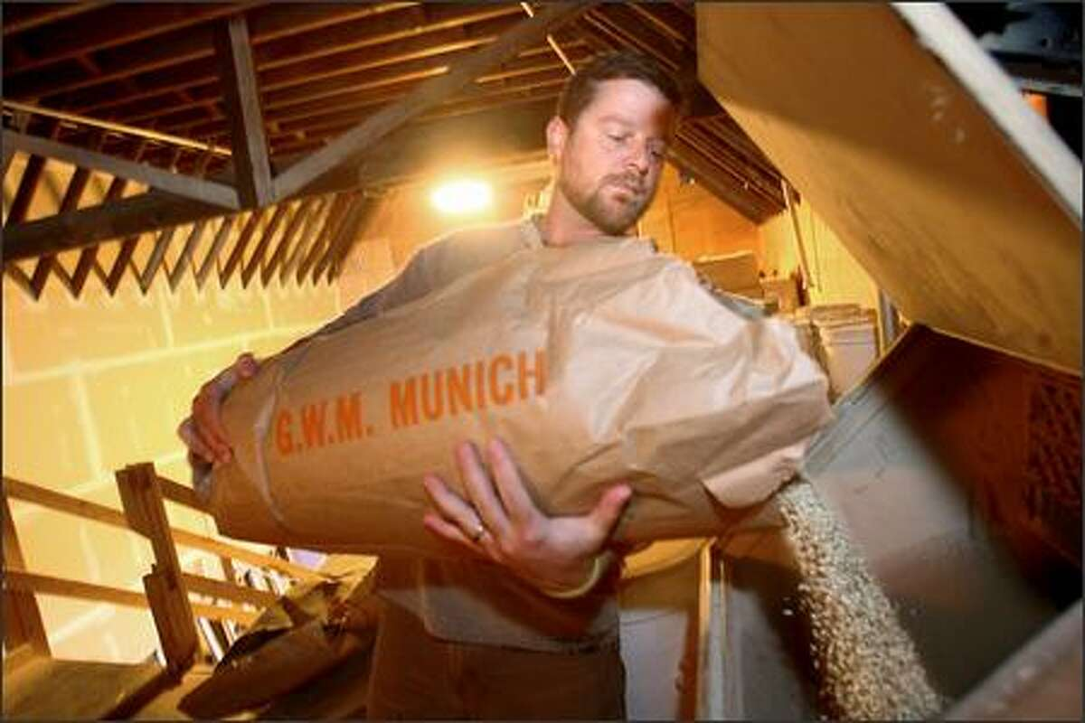 """Rudyard """"J."""" Kipling, head brewer/production manager, dumps a bag of malted barley into the mix that makes Hale's Mongoose India Pale Ale. The prices of hops and barley, two of the essential ingredients in brewing, continue to rise, as do the costs of shipping and bottling."""
