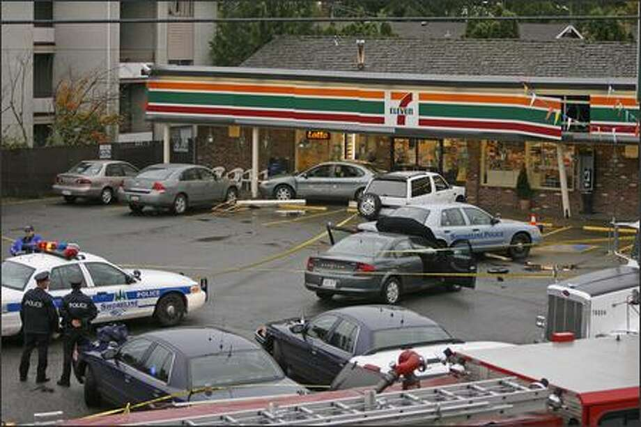 Police look over scene where a chase ended in a 7-Eleven parking lot after the suspect, who drove into an unmarked police vehicle, was shot. The suspect's car is under the Lotto sign by the front door. Photo: Grant M. Haller/Seattle Post-Intelligencer