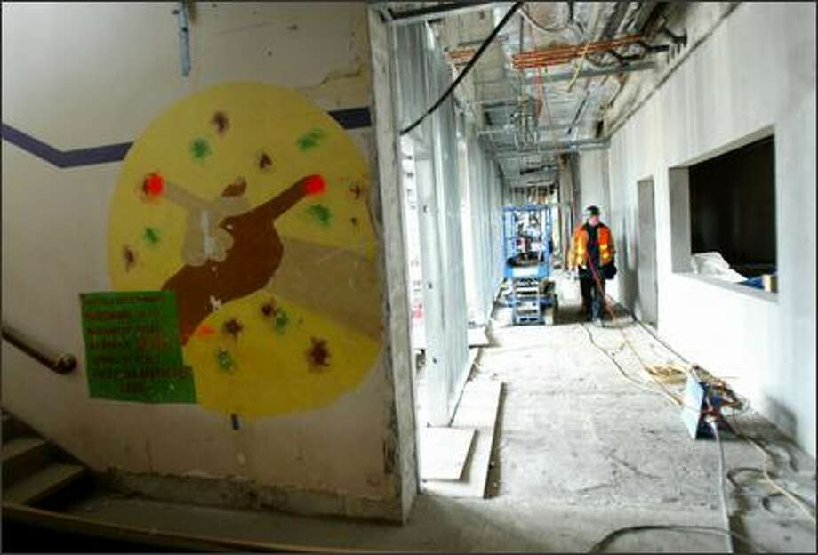 Construction workers walk down a hallway in Seattle's Garfield High School on Thursday during a remodeling project there. Photo: Joshua Trujillo/Seattle Post-Intelligencer
