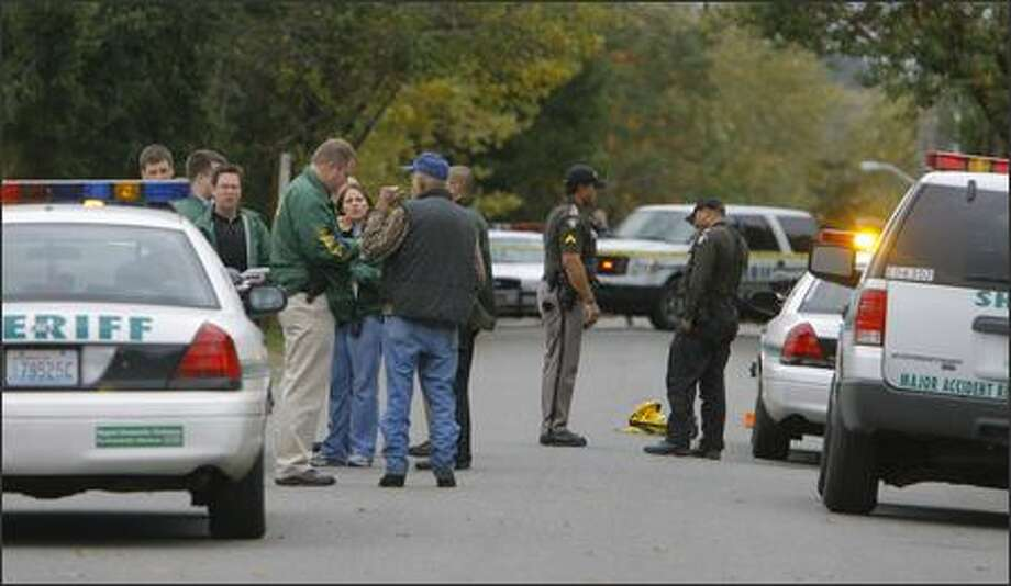 King County sheriff's investigators talk to a neighbor after Friday's shooting death of Craig Robert Hoffman. Hoffman died after apparently interrupting three burglars at his home in White Center. Photo: Gilbert W. Arias/Seattle Post-Intelligencer