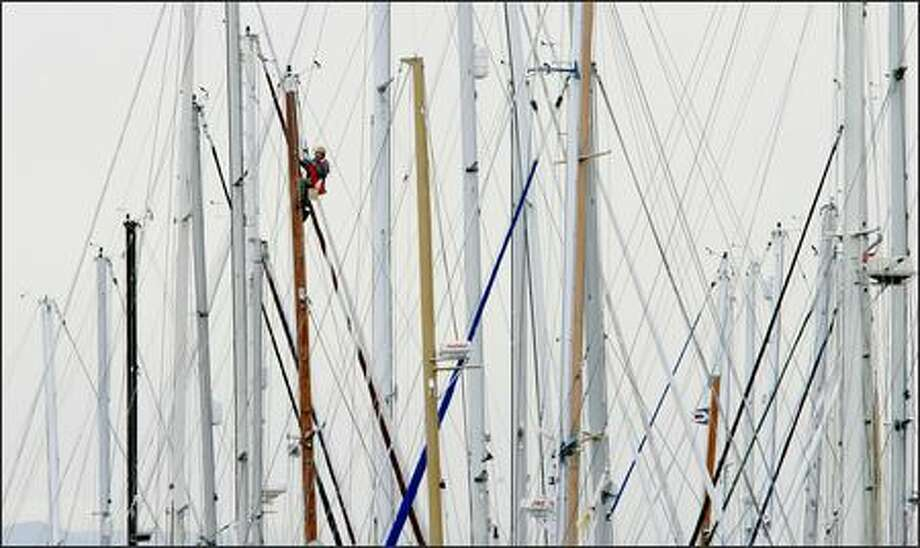 Doug Nine paints the mast of his 36' Cape George sailboat at Shilshole Marina on Thursday. Nine said the sailboat is all he owns and has lived on boats for 16 years. Photo: Dan DeLong/Seattle Post-Intelligencer