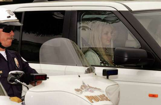 Britney Spears, sitting in the front left passenger seat, is driven away from Los Angeles County Superior court, escorted by Los Angeles Police officers, after a custody hearing Tuesday, May 6, 2008, in Los Angeles. Photo: Damian Dovarganes, AP / AP