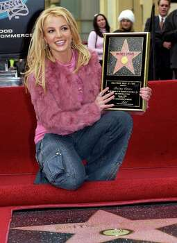 ** FOR IMMEDIATE RELEASE--FILE **Pop star Britney Spears poses for photographers with her new star on the Hollywood Walk of Fame, in this Nov. 17, 2003, file photo in Los Angeles. Photo: NICK UT, AP / AP