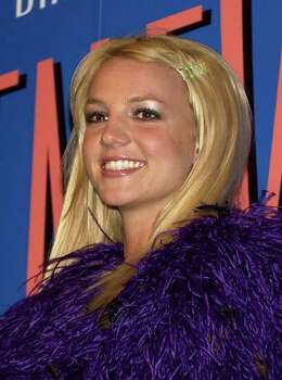 "Britney Spears smiles during a press conference at a Tokyo hotel to promote her latest album ""In the Zone"" Friday, Dec. 12, 2003. Spears is currently on the promotion tour in Asia. Photo: CHIAKI TSUKUMO, AP / AP"